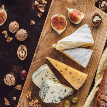 food composition with assorted cheese, figs and hazelnuts on dark tabletop