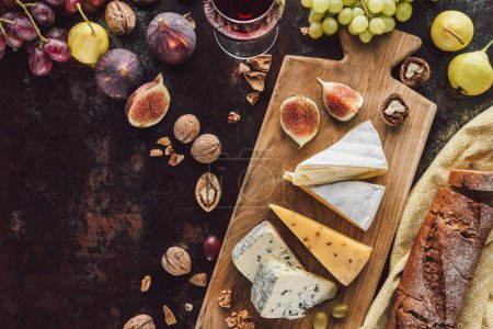 food composition with assorted cheese, glass of wine and fruits on dark tabletop
