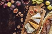 """Постер, картина, фотообои """"состав пищи с ассорти из сыров, стакан вина и фрукты на темной столешницей"""""""