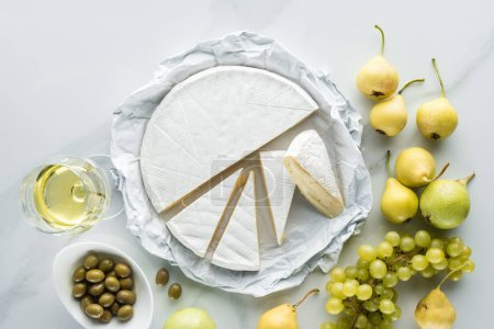 flat lay with glass of wine, brie cheese, olives and fruits on white marble surface