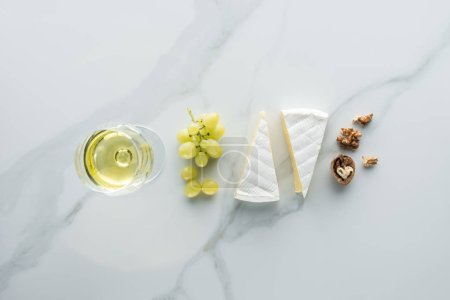 flat lay with glass of wine, camembert cheese and hazelnuts on white marble surface