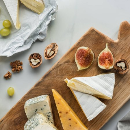 Photo for Flat lay with food composition of cheese and fig pieces on cutting board on white marble surface - Royalty Free Image