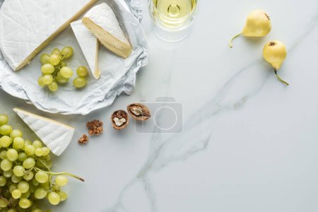 flat lay with glass of wine, camembert cheese, pears and grape on white marble surface