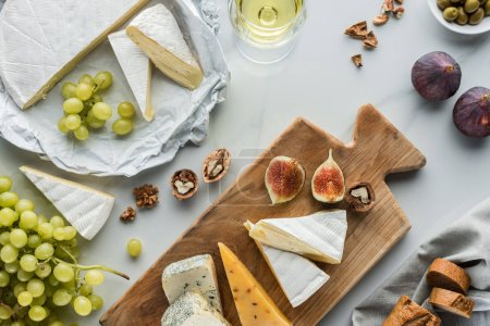 Photo for Flat lay with food composition of cheese and fig pieces on cutting board, fruits and glass of wine on white marble surface - Royalty Free Image