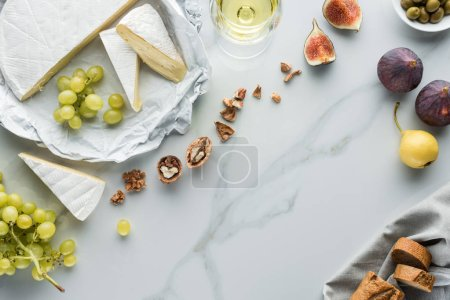 flat lay with cheese, wine and fruits arranged on white marble surface