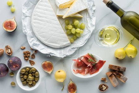 Photo for Flat lay with wine, camembert cheese, jamon, figs, grape and bread on white marble tabletop - Royalty Free Image