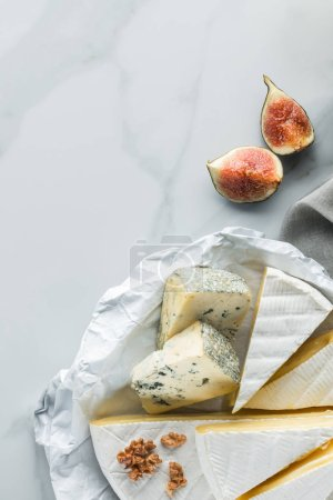 Photo for Flat lay with assorted cheese and fig pieces on white marble surface - Royalty Free Image