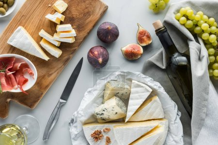Photo for Flat lay with wine, cheese, jamon, figs and grape arranged on white marble tabletop - Royalty Free Image