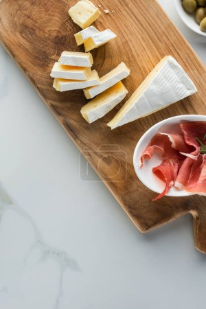 flat lay with camembert cheese and jamon on wooden cutting board on white marble tabletop