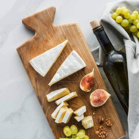 flat lay with food composition of camembert cheese on cutting board and wine on white marble surface