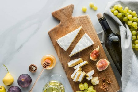 Photo for Flat lay with food composition of cheese on cutting board, honey, wine and fruits on white marble surface - Royalty Free Image
