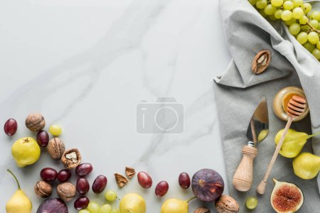 food composition with fruits, honey and linen on white marble tabletop