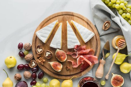flat lay with cheese, jamon, figs, hazelnuts and grape on wooden board on white marble tabletop