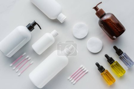 Photo for Top view of bottles of cream, natural oils and cosmetic pads on white surface, beauty concept - Royalty Free Image