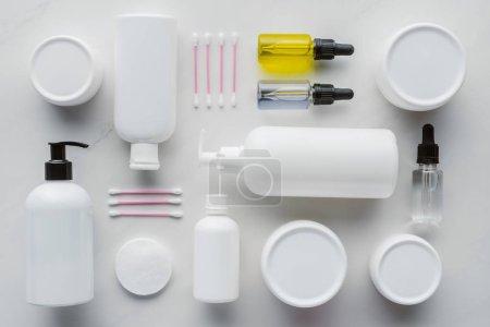 Photo pour Lay plat avec des bouteilles de crème, huiles naturelles et ouatés sur le concept de beauté blanc surface, - image libre de droit