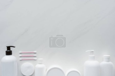 Photo for Top view of bottles of cream, cosmetic pads and cotton swabs on white surface, beauty concept - Royalty Free Image