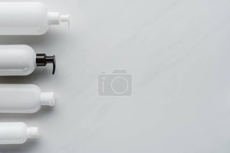 top view of bottles of lotion on white surface, beauty concept