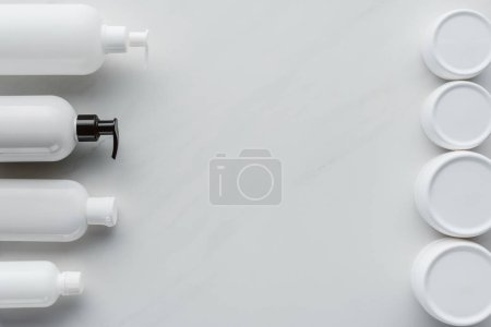 top view of bottles of cream and lotion on white surface, beauty concept
