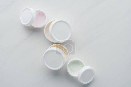 Photo pour Vue de dessus des bouteilles ouvertes de crème sur le concept de beauté surface, blanc - image libre de droit