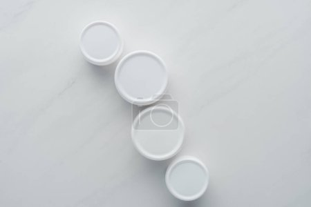 Photo for Top view of bottles of cream on white surface, beauty concept - Royalty Free Image