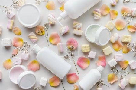 Photo pour Vue de dessus des bouteilles de crème, de pétales de rose et de guimauves sur le concept de beauté sur table, blanc - image libre de droit