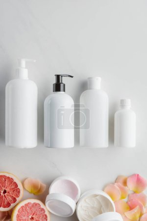 top view of bottles of cream, pieces of grapefruit and rose petals on white surface, beauty concept