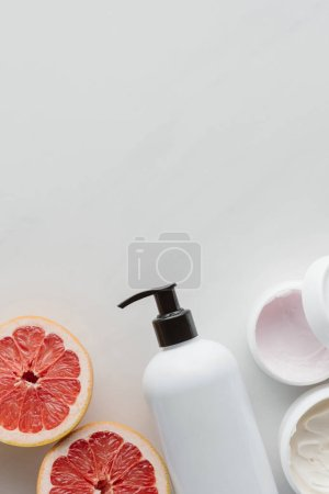 top view of bottle of cream and pieces of ripe grapefruit on white surface, beauty concept