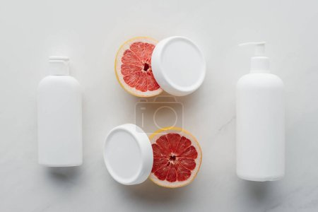elevated view of bottles of cream and pieces of grapefruit on white surface, beauty concept