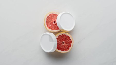 top view of bottles of cream and pieces of grapefruit on white surface, beauty concept
