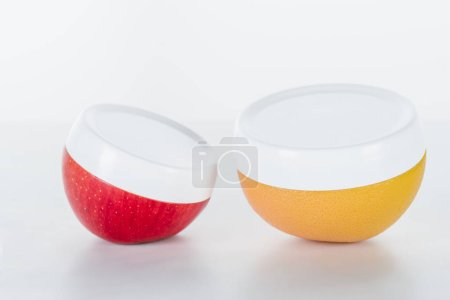 red and orange bottles of cream on white surface, beauty concept
