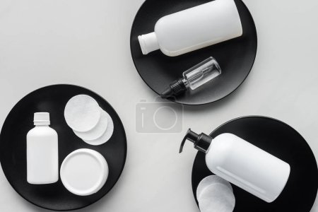 elevated view of bottles of cream and cosmetic pads on three black plates, beauty concept