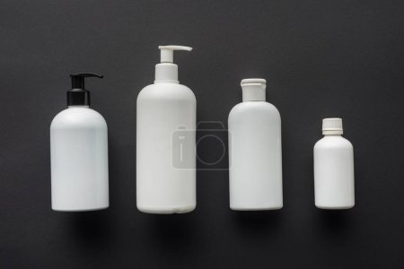 top view of four white bottles of cream isolated on black, beauty concept