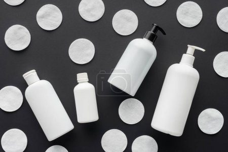 top view of scattered bottles of cream and cosmetic cotton pads isolated on black, beauty concept