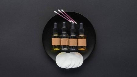 Photo pour Vue de dessus des bouteilles d'huiles naturelles et tampons sur plaque, concept de beauté - image libre de droit