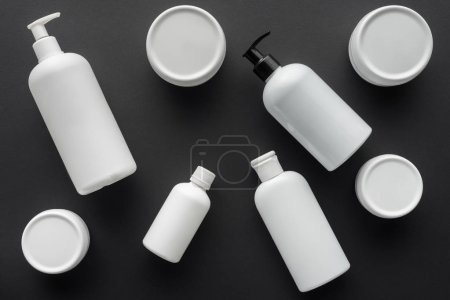 top view of scattered white bottles of cream isolated on black, beauty concept