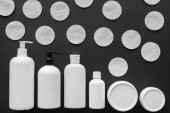 top view of bottles of cream and cosmetic cotton pads isolated on black, beauty concept