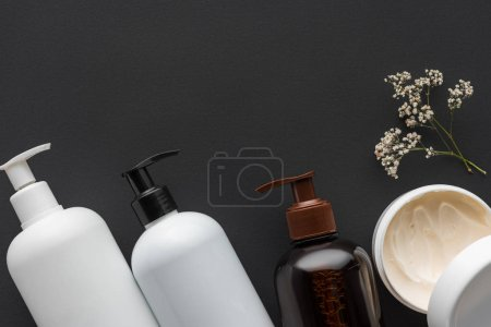 top view of bottles of cream and dried flowers isolated on black, beauty concept