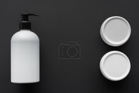 top view of bottles of lotion and cream isolated on black, beauty concept