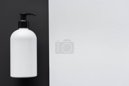 elevated view of bottle of cream on black and white surface, beauty concept