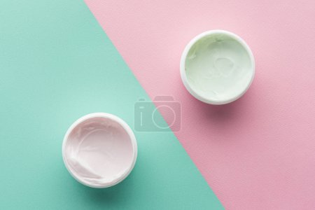 top view of bottles of cream on pink and green surface, beauty concept
