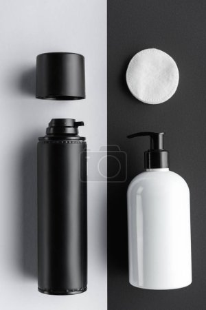 top view of bottles of cream and cosmetic pads on black and white surface, beauty concept