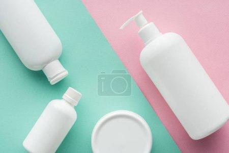 Photo pour Vue du dessus des bouteilles de crème sur surface verte et rose, concept beauté - image libre de droit