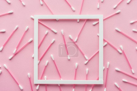 top view of cotton swabs with white frame isolated on pink, beauty concept