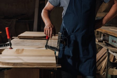partial view of woodworker standing akimbo at wooden workshop