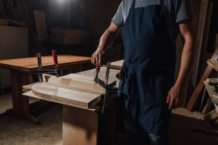 Photo for Partial view of woodworker standing at wooden workshop - Royalty Free Image