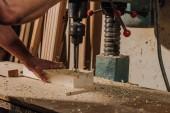 vue partielle de l'ébéniste utilisant électrique percer sur bois à l'atelier