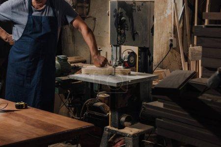 Photo pour Vue partielle de l'ébéniste debout près d'une perceuse électrique à l'atelier en bois - image libre de droit
