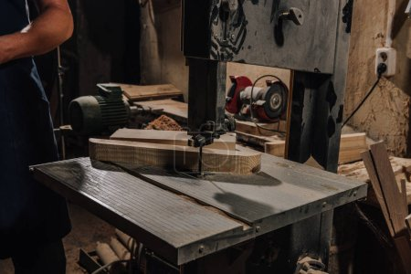 partial view of woodworker at wooden workshop