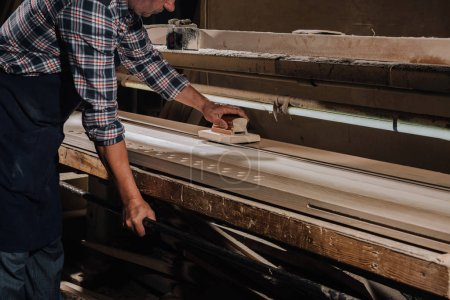 Photo for Cropped shot of woodworker planing wood with hand plane at workshop - Royalty Free Image