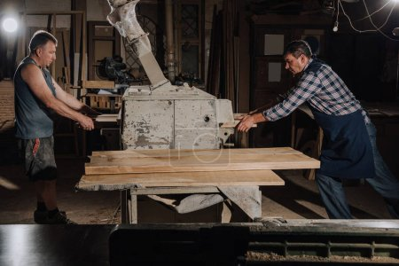 Photo for Carpenters working with wooden planks at wooden workshop - Royalty Free Image